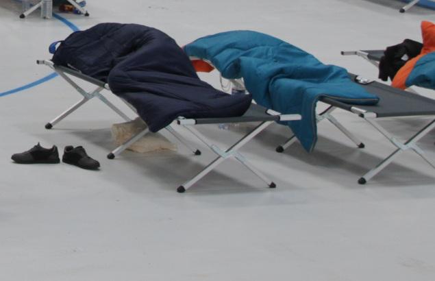 Deux lits de camps recouverts de devets sur la patinoire de Cergy
