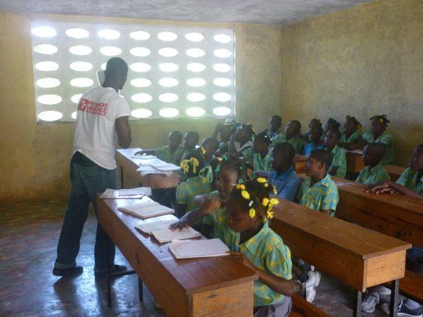 Un formateur sensibilise les écoliers dans une salle de classe aux pratiques d'hygiène