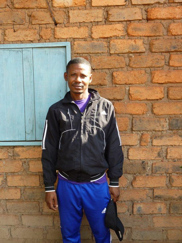 Hamidou pose devant le mur de sa maison dans la zone PK5 de Bangui