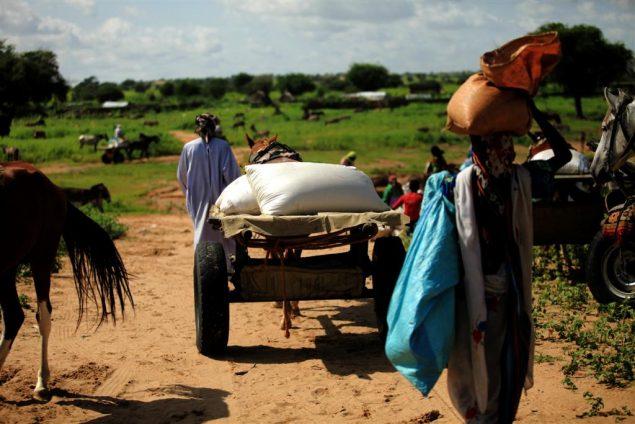 Un homme transporte un sac de vivres sur la tête