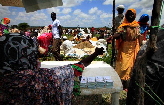 Une femme donne un coupon à une bénéficiaire lors d'une distribution de nourriture.