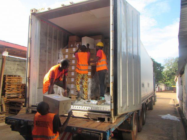 Des hommes chargent un camion rempli de palettes
