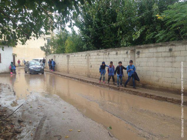 Des enfants marchent sur un trottoir près d'une rue inondée