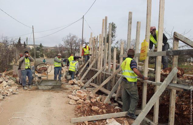 Des ouvriers construisent un mur près de l'école Jaloud