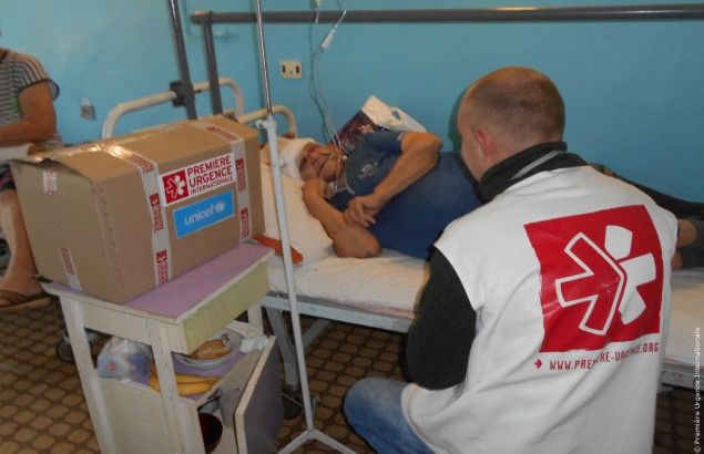 Valentina, in her hospital bed, is receiving the visit of Première Urgence Internationale staffs