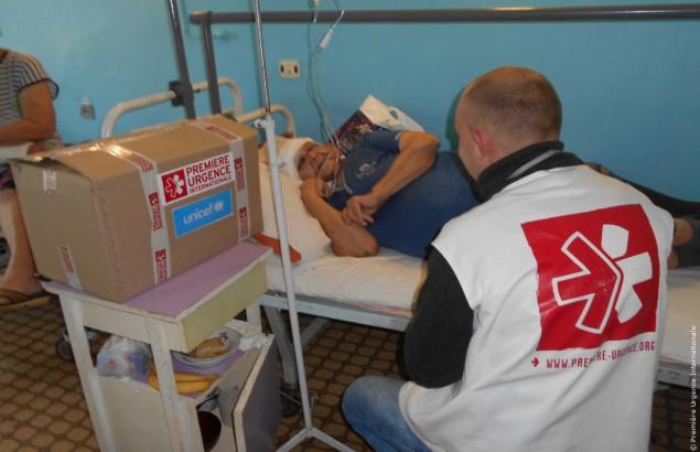 Valentina, dans son lit d'hôpital, reçoit la visite des équipes de Première Urgence Internationale