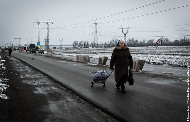 A little lady is crossin a checkpoint at Mariinka