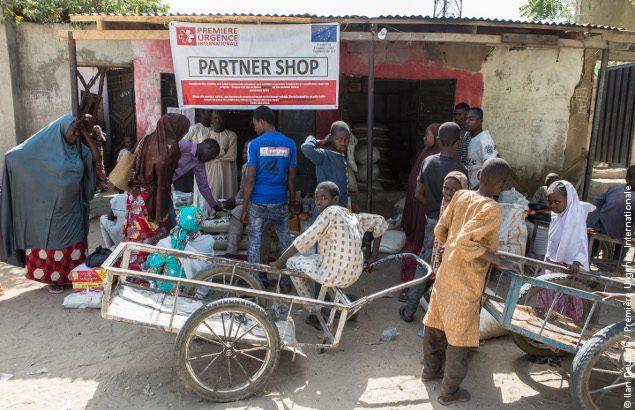 Personnes devant une boutique partenaire du projet innovant au Nigeria de Première Urgence Internationale