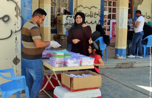 Une femme vient récupérer des médicaments après une consultation faisant partie du programme de Première Urgence Internationale de fournir des soins de santé en Irak